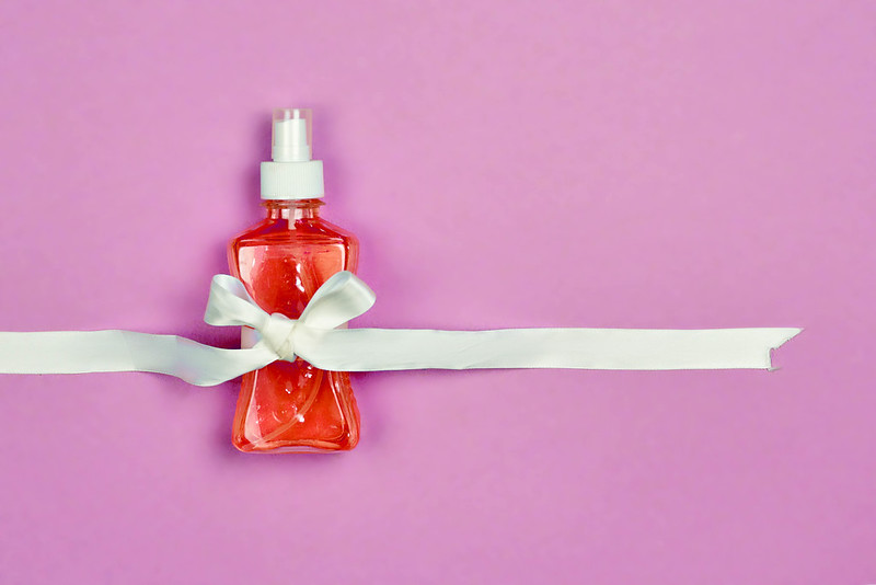 a bottle of disinfectant hand sanitizer with a bow around it