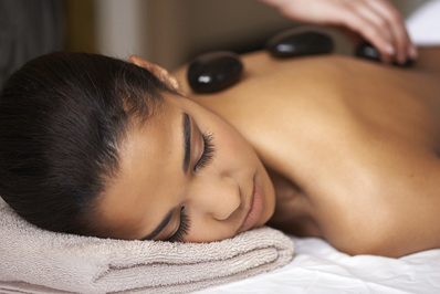 A woman relaxes to a warm, calming hot stone massage.